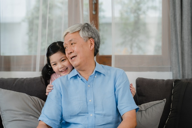 Asian grandfather talking with granddaughter at home. senior chinese, grandpa happy relax with young granddaughter girl using family time relax with young girl kid lying on sofa in living room.