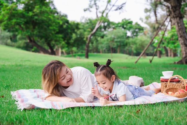 Asian grandmother and granddaughter laying on the green glass field outdoor, family enjoying picnic together in summer day