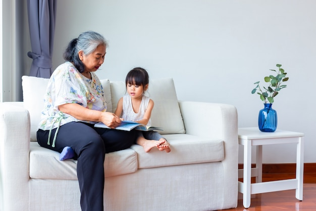 Asian grandmother and granddaughter in living room