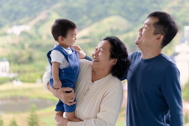 Asian grandmother is holding the little baby boy grandson and the boy laughing with father.