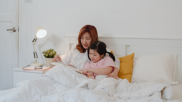 Asian grandmother read fairy tales to granddaughter at home. senior chinese, grandma happy relax with young girl enjoy good quality time lying on bed in bedroom at home at night concept.