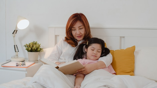 Asian grandmother read fairy tales to granddaughter at home. senior chinese, grandma happy relax with young girl who sleep while listening to tales lying on bed in bedroom at home at night concept.