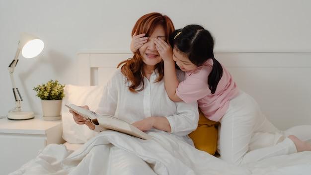 アジアの祖母は家でくつろいでいます。シニア中国人、おばあちゃんは若い孫娘の女の子と一緒にリラックスして夜のコンセプトで自宅の寝室のベッドに横たわって一緒に遊んで彼女の目の驚きをお楽しみください。