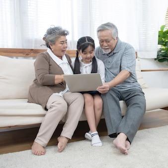 Азиатские бабушка и дедушка с маленьким молодым внуком сидит на диване и играет