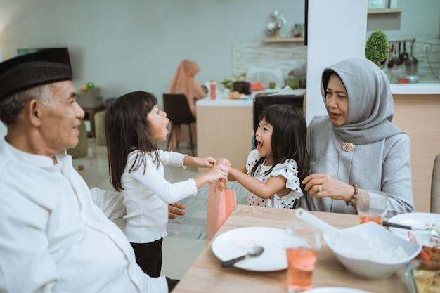 Asian grandparents giving a present to grandchildren during eid mubarak celebration at home