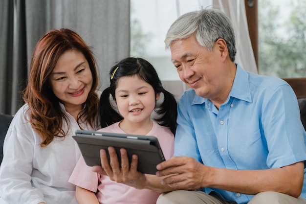 Asian grandparents and granddaughter video call at home. senior chinese, grandpa and grandma happy with girl using mobile phone video call talking with dad and mom lying in living room at home.
