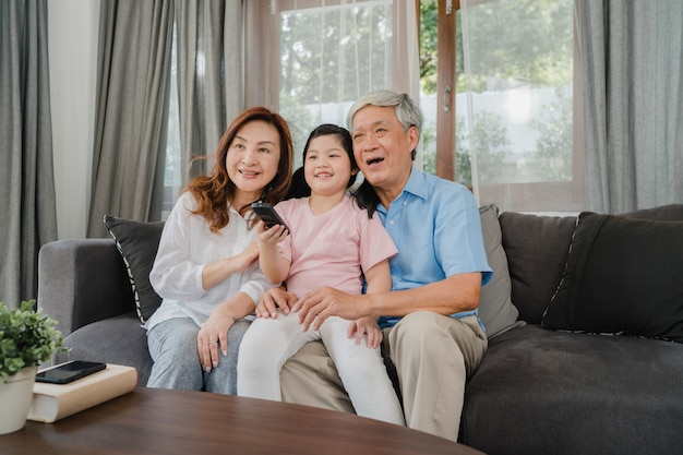 Asian grandparents watch tv with granddaughter at home. senior chinese, grandfather and grandmother happy using family time relax with young girl kid lying on sofa in living room concept.