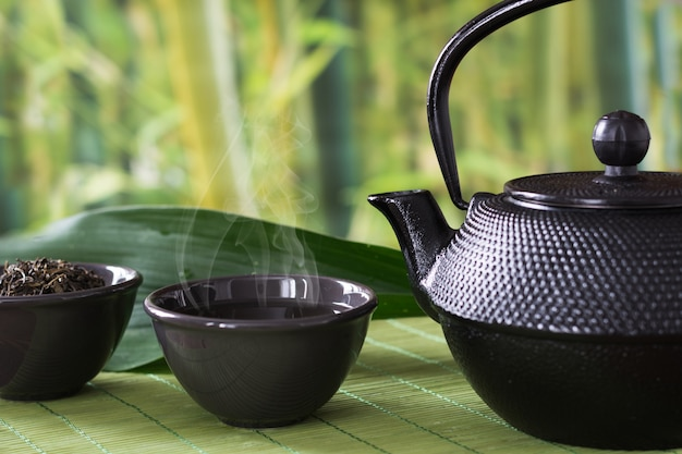 Asian green tea set with black china kettle on bamboo mat with dried green tea in bowl.