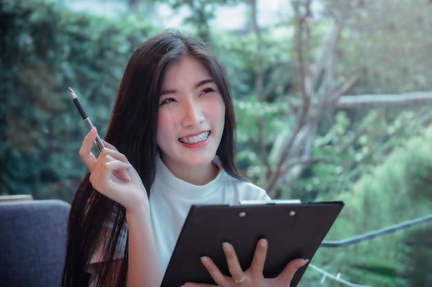 Деловой стиль азиатского гриля держать ручку и улыбаться, эмоции, позитивная вещь дня