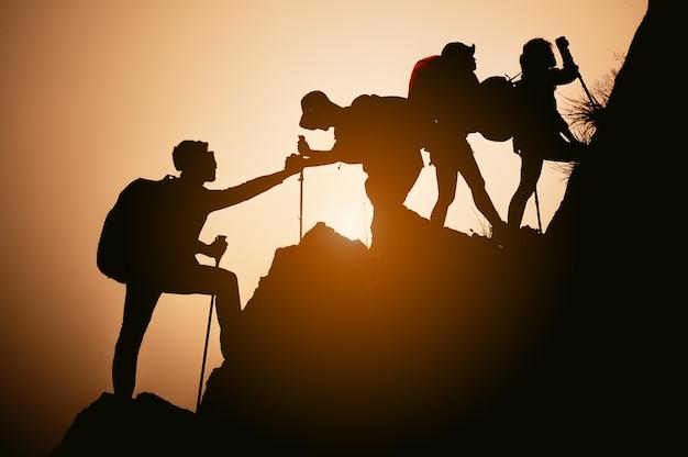 산에 등반 하는 아시아 그룹입니다. 도움의 손길을 주고. 등반, 도움 및 팀 작업 개념