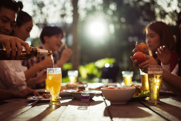 Asian group eating and drinking cold beer outside the house at night