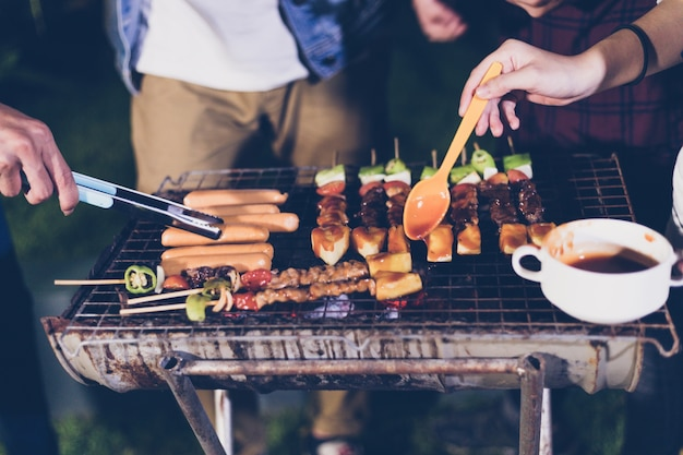 Asian group of friends having outdoor garden barbecue