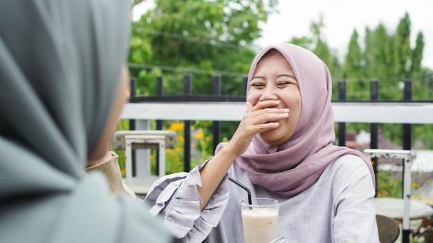 Asian group hijab woman smilling in cafe with friend
