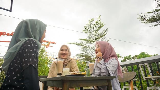 Азиатская группа хиджаб женщина улыбается в кафе с другом