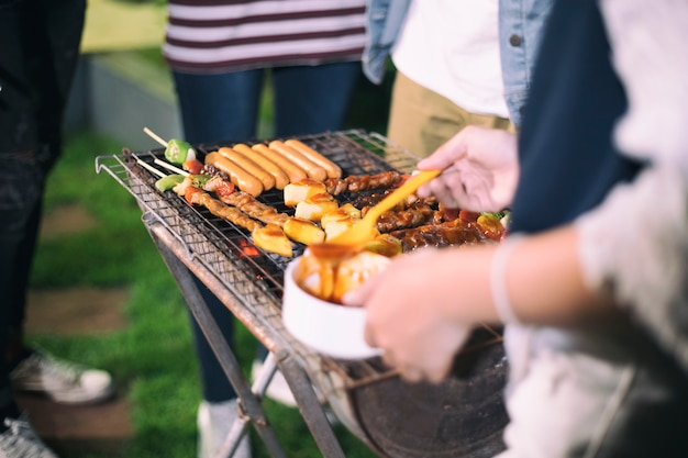 屋外の庭で火事のパーティーでバーベキューやグリルのシャークライクを作っているアジアのグループ