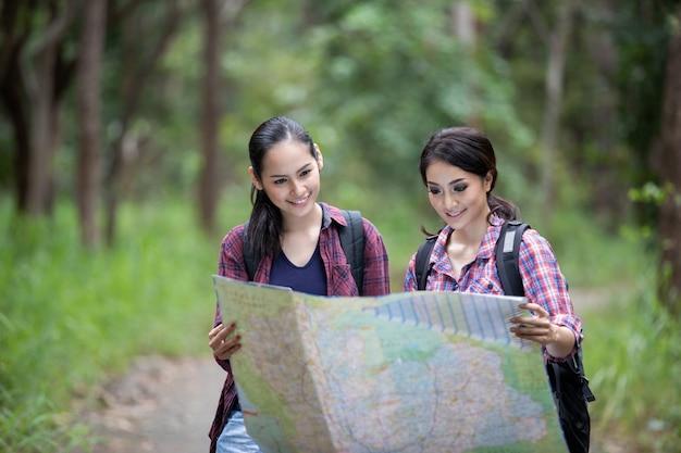 一緒に歩いて、地図を探している友人のバックパックとハイキングの若者のアジアグループ
