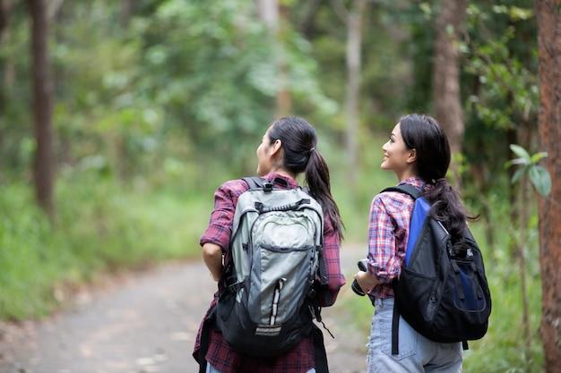 森の中を一緒に歩いている友人のバックパックとハイキングの若者のアジアグループ