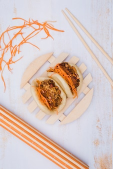 Asian gua bao served on circular wooden plate with chopsticks and grated carrot on wooden surface