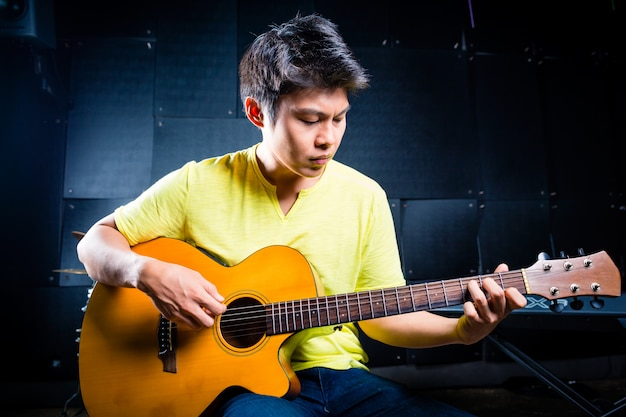 Asian guitarist playing music in recording studio