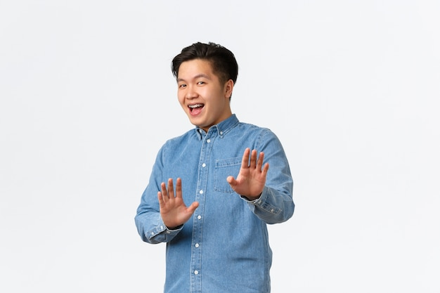 Asian guy feeling awkward, apologizing and step back, raising hands up in stop gesture, politely rejecting offer, saying no thank you, refusing something, smiling, standing white wall