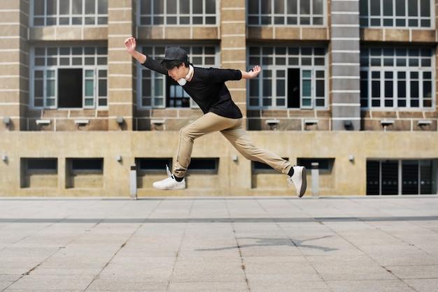 Азиатский парень midair jumpshot на открытом воздухе