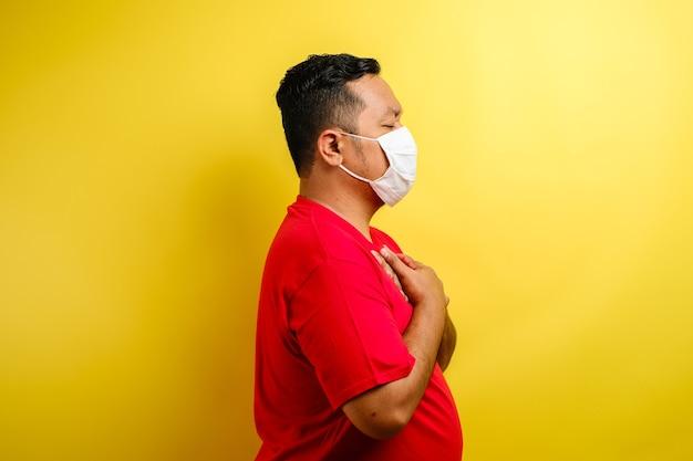胸に痛みを感じるマスクを身に着けているアジア人の男、左胸を保持するジェスチャー。黄色の背景