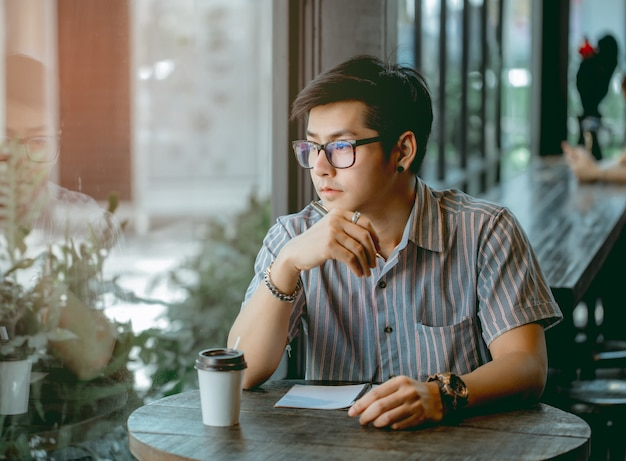 Asian guy with glasses sitting and writing something with thought.