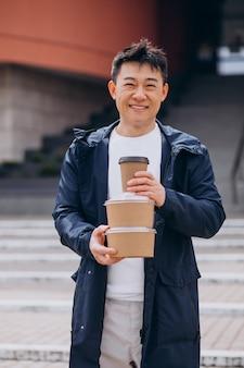 テイクアウトのフードボックスを持つアジア人の男