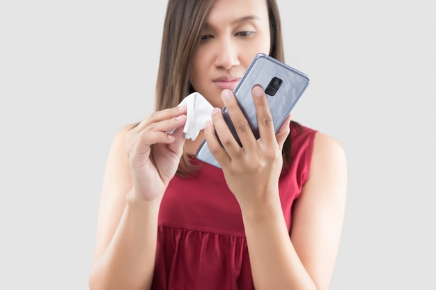 Asian hands woman cleaning her mobile phone on screen with the microfiber cloth on a gray background