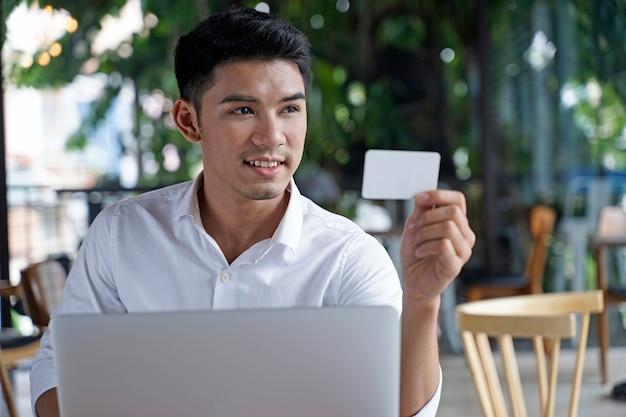 クレジットまたはデビット支払いを使用してアジアのハンサムなビジネスマンまたはサラリーマンまたは若い学生