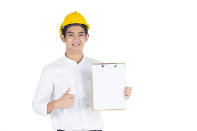Asian handsome businessman wearing a yellow safety helmet holding and showing a thumb up a clipboard in his hand close up, isolated on white  white copyspace.