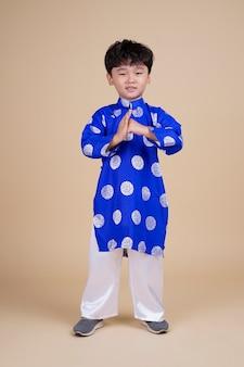 Азиатский красивый милый маленький мальчик с прекрасным выражением лица в традиционной вьетнамской одежде во время отпуска
