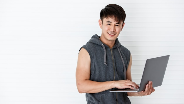 Asian handsome fit smiling man holding hand laptop computer to learning exercise wearing sleeveless t-shirt gray sportswear in white background.