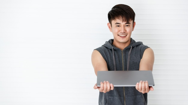 Asian handsome fit smiling man stand hand over a laptop computer wearing sleeveless t-shirt gray sportswear in white background.