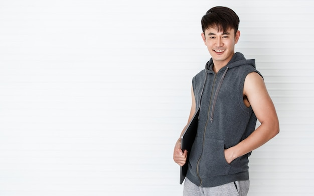 Asian handsome fit smiling man stand pose holding hand laptop computer wearing sleeveless t-shirt gray sportswear in white background.