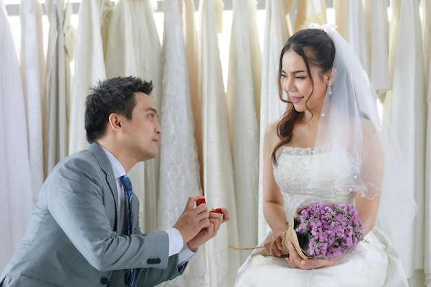 Asian handsome groom in grey formal suit kneeling holding red box of diamond ring proposing young beautiful happy bride in white wedding dress with hair veil holding flower bouquet in dressing room.