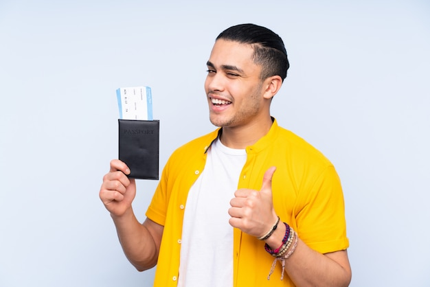 Asian handsome man on blue wall in vacation holding a passport and plane with thumb up