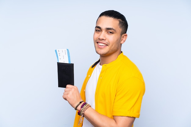 Asian handsome man isolated on blue background happy in vacation with passport and plane tickets