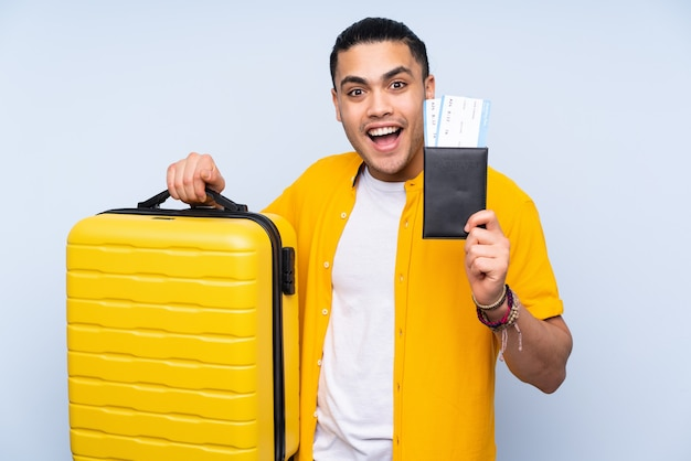 Asian handsome man isolated on blue background in vacation with suitcase and passport and surprised