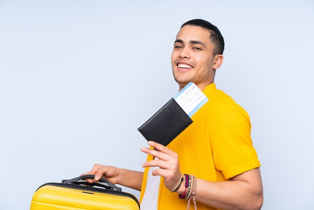 Asian handsome man isolated on blue background in vacation with suitcase and passport