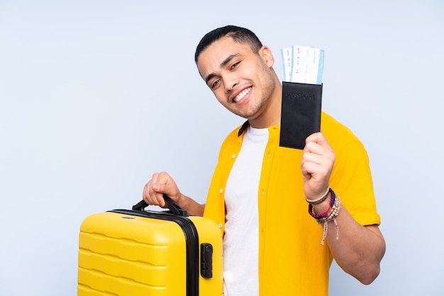 Asian handsome man isolated on blue in vacation with suitcase and passport