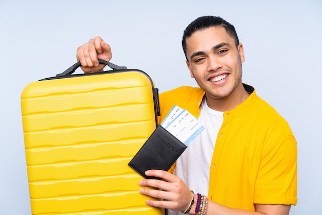 Asian handsome man isolated on blue wall in vacation with suitcase and passport