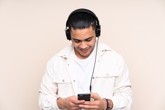Азиатский красавец изолирован на бежевом фоне, слушает музыку и смотрит на мобильный
