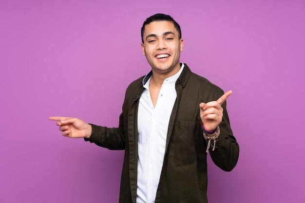 측면에 손가락을 가리키는 파란색 벽에 고립 된 아시아 잘 생긴 남자와 행복