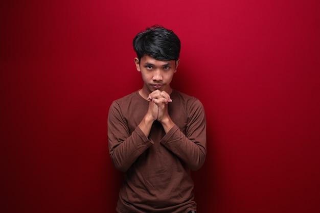 赤い背景で隔離のアジアのハンサムな男は、手のひらを一緒に保ちます