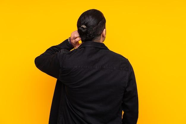 선 포즈에서 노란색 배경에 고립 된 아시아 잘 생긴 남자