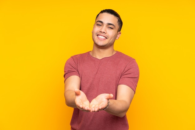 Asian handsome man isolated on yellow background keeps palm together. person asks for something