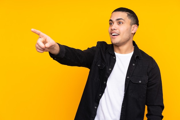 Asian handsome man isolated on yellow frustrated and pointing to the front