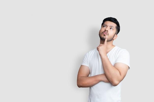 孤立した白い背景を見上げながら疑問を持っている白いtシャツのアジアのハンサムな男