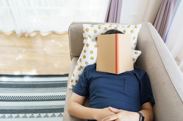アジアのハンサムな男が寝ている間に本を読みます。